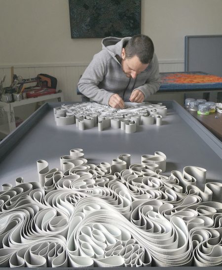 Jason Hallman works on one of Stallman's sculptural canvases.