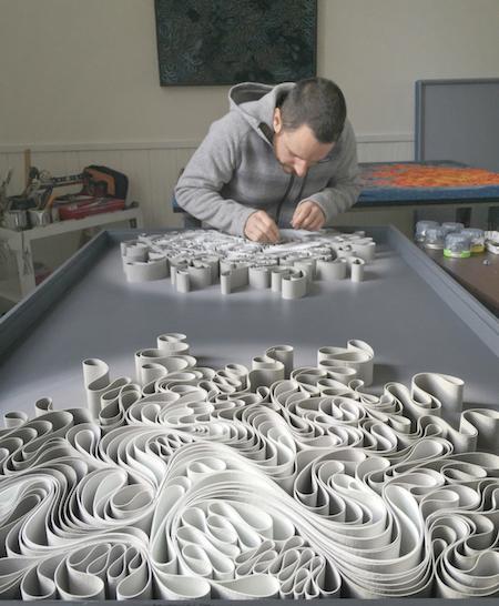Jason Hallman works on one of Stallman's sculptural canvases.